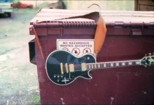 Guitar slung over dumpster