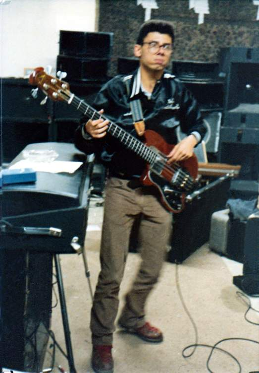 Bob Lowden plays his Ovation bass in front of a wall of PA equipment.